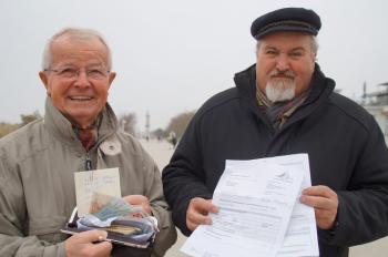 Walter Vogt (li.) zeigt voller Stolz das aus Stollen- und Glühweinverkauf eingespielte Geld für den guten Zweck. Leuchtturmchef Klaus Möller präsentiert die Gebührenrechnung der Stadt Rostock.