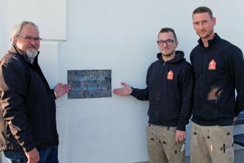 Endlich: Leuchtturmchef Klaus Möller und die beiden Steinmetzgesellen Ole Kaube und Hannes Fleischer (v.l.) konnten ein Warnemünder Problem lösen: Die Hochwassermarke am Lotsenhaus ist wieder gut erkennbar.