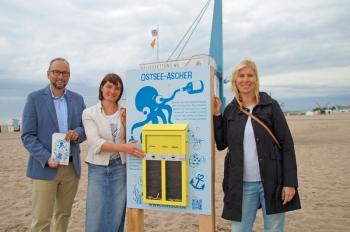 Tourismusdirektor Matthias Fromm, EUCC-Geschäftsführerin Nardine Stybel und Kristin Plühmer, als Verantwortliche für Umweltmanagement in der Tourismuszentrale Rostock & Warnemünde, präsentieren den neuen Ostsee-Ascher am Rettungsturm 3.