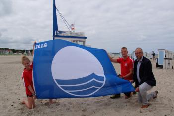 """Sie hissen die """"Blaue Flagge"""" am Strand von Warnemünde: die Rettungsschwimmer der DRK-Wasserwacht Alexandra Sievert und Arian Baume und Tourismusdirektor Matthias Fromm (v.l.)."""