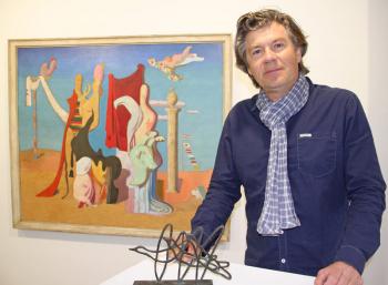 Der Warnemünder Galerist Alexander Gehrke vor dem Gemälde