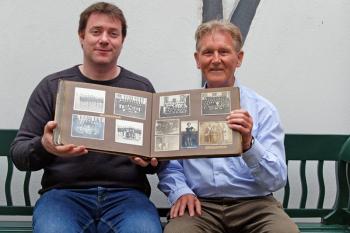 """Christoph Wegner (l.) und Eckart Peters mit dem Sportalbum des """"Männer Turnverein Warnemünde"""". Es wurde dem Heimatmuseum durch die Warnemünder Familie Stalbohm überreicht."""