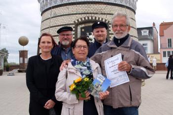 Für das Urlauberpaar Bärbel und Manfred Forwerk ist es der erste Besuch auf dem Warnemünder Leuchtturm. Inge Morenz, Klaus Möller und Mathias Stagat begrüßen die Jubiläumsgäste (hintere Reihe v.l.).