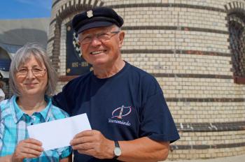 Leuchtturm-Schatzmeister Walter Vogt übergibt einen mit 300 Euro gefüllten Umschlag an Küsterin Silvia Schmidt.