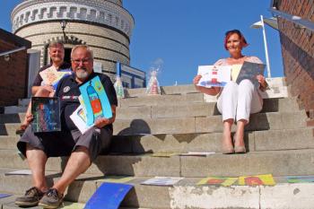 """Freuen sich über die vielen phantasievollen Arbeiten zum Thema """"120 Jahre Leuchtturm"""": Mathias Stagat, Klaus Möller und Inge Morenz, ebenfalls Vorstandsmitglied im Verein (v.l.)."""