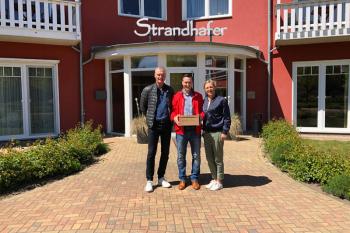 Die Inhaber des Strandhafer Aparthotels, Dorett und Christian Scheil, fühlen sich dem SV Warnemünde Fußball e.V. seit vielen Jahren verbunden. Vorstandsmitglied Mike Frahm (mitte) freut sich über die großzügige finanzielle Unterstützung.