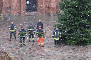 Der Baum steht und dazu schneit es noch! Die Kameraden der Freiwilligen Feuerwehr Warnemünde haben ganze Arbeit geleistet. Zur Abnahme gesellte sich sogar noch Rostocks Oberbürgermeister Claus Ruhe Madsen (hinten rechts) hinzu.