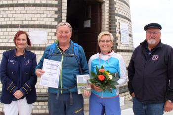 Eine freudige Überraschung für die beiden Fahrradurlauber Christa und Joachim Graf (m.) aus Tirol: Die Arztassistentin wurde als 30.000. Leuchtturmbesucherin des Jahres 2019 auserkoren. Inge Morenz (l.) und Klaus Möller vom Leuchtturmverein beglückwünschten das sportliche Paar.